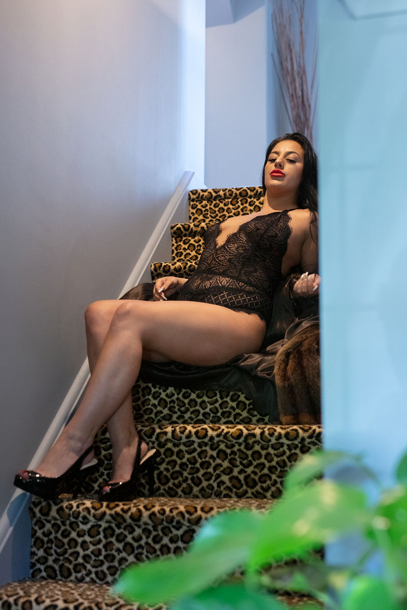 Lady in black lingerie sitting on stairs