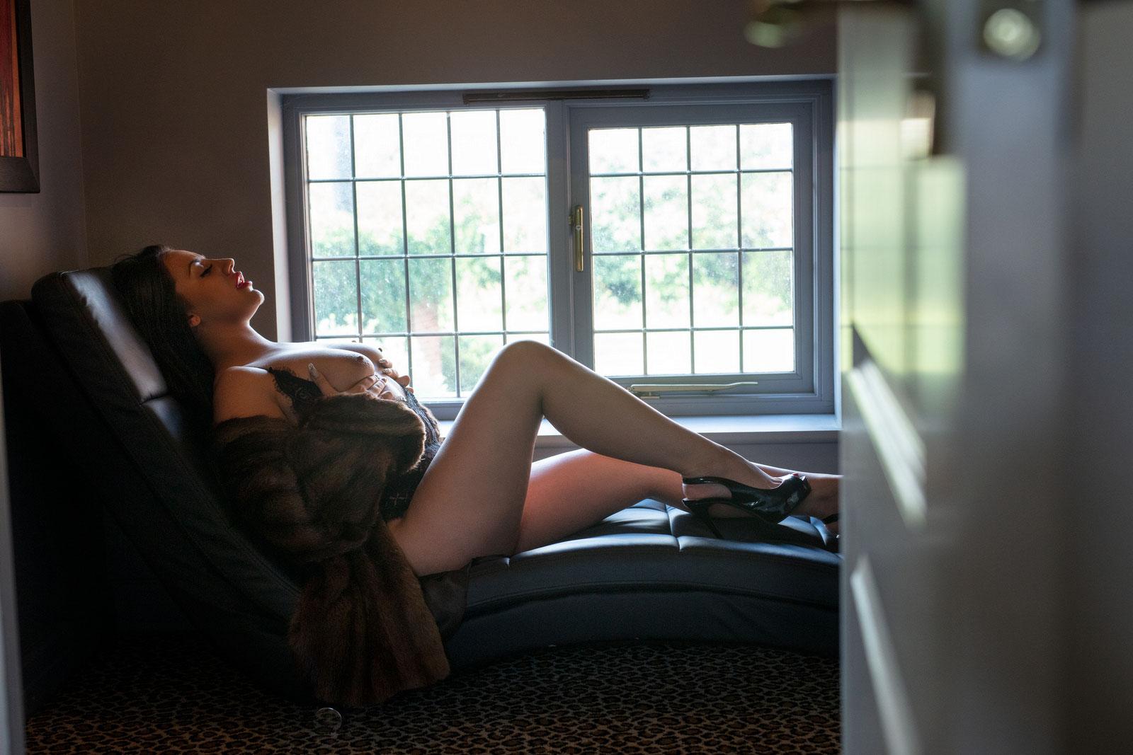 Eritic lady lay on chair near a window