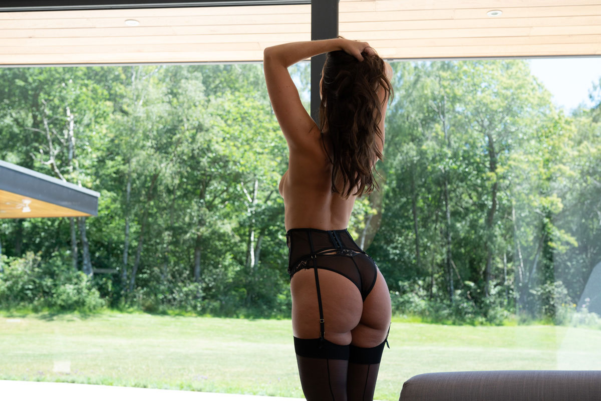 Woman in black lingerie looking at green trees
